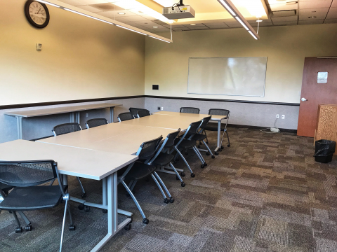 Upstairs Conference Room showing tables put together to resemble conference table, chairs, and white board mounted on wall